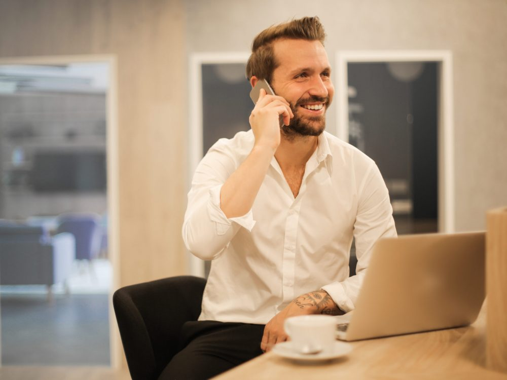 smiling-formal-male-with-laptop-chatting-via-phone-3760263